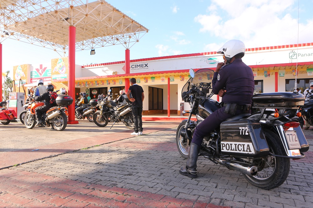 Motorcycle cop tour group gas station Cuba