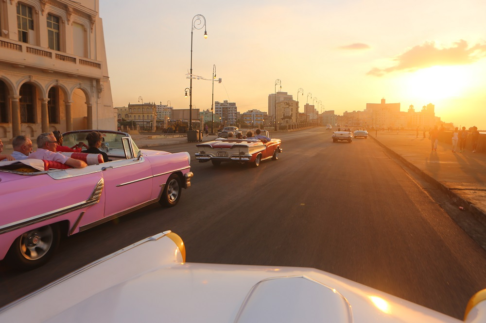 us tour group visitors classic american cars sunset malecon havana cuba